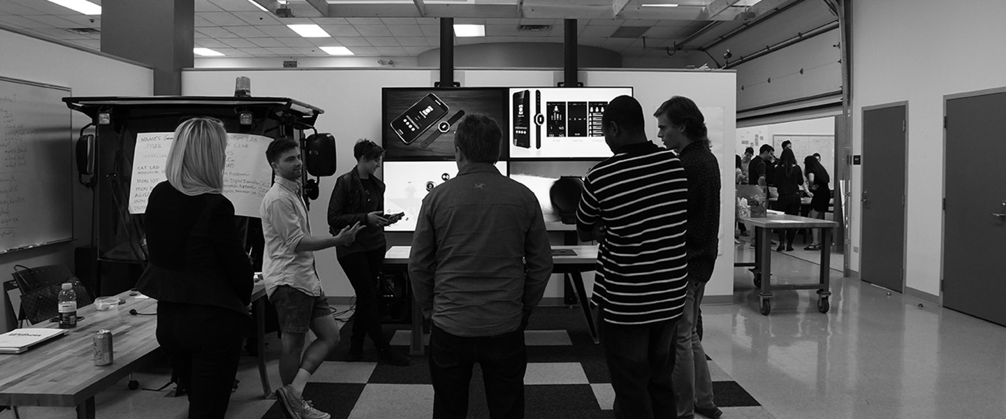 A group of students and partners standing around 4 televisions and talking about the work on the screens.